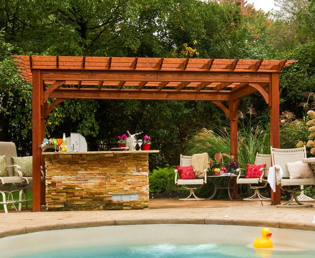 traditional wooden pergola over outdoor kitchen island