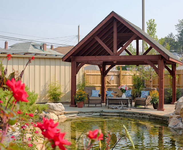 Alpine Cedar Wood Pavilion in Mahogany Stain by Pond with Sitting Chairs