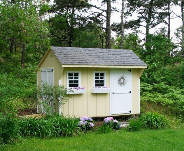 Backyard Quaker in Cream with White Wood Doors and Flower Boxes in a Backyard