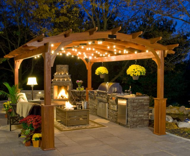 Hearthside Pergola on a Patio with Outdoor Kitchen Island and Lights
