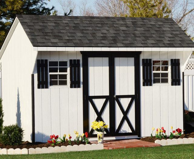Backyard Quaker Storage Shed in White T-111 in a Garden