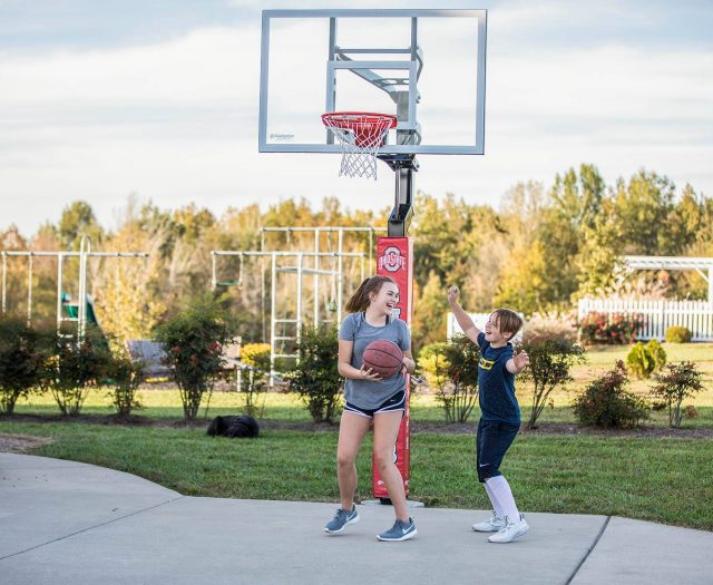 Two Kids Playing Basketball Outside with Goalsetter Basketball System