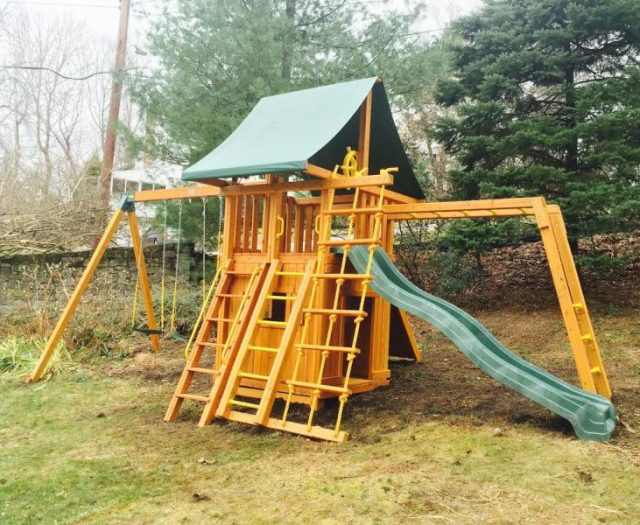 Dream Cedar Swing Set Installed on a Slight Hill with Bottom Clubhouse
