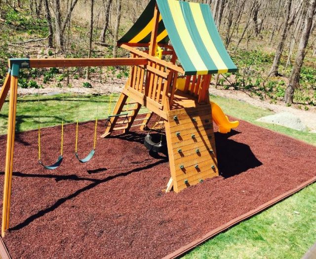 Supreme Swing Set installed in red rubber mulch on Sloped Backyard