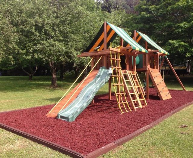 Dream Swing Sets connected with green crawl tube installed in red rubber mulch