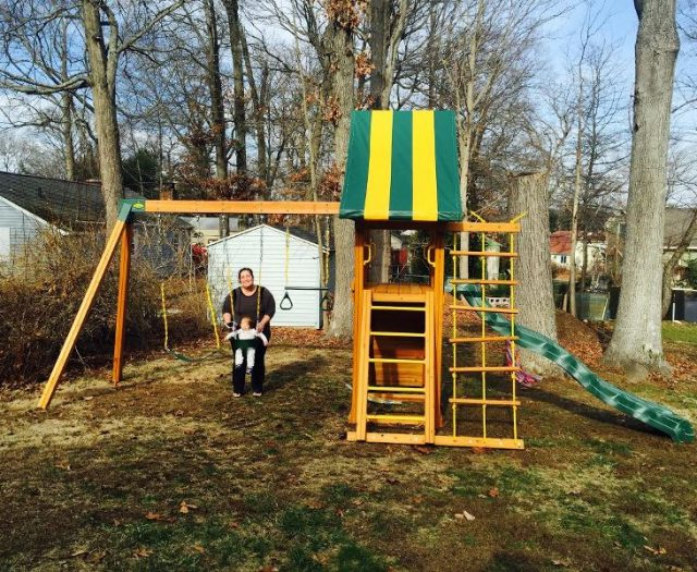 Dreamscape Cedar Playset with striped tent and happy customers