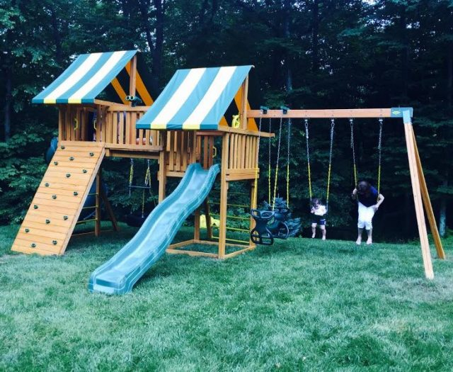 Family In New Fantasy Swing Set in Backyard