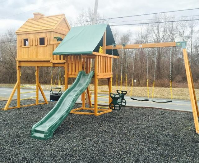 Fantasy Treehouse Backyard Swing Set Installed on Black Mulch With Green Tent