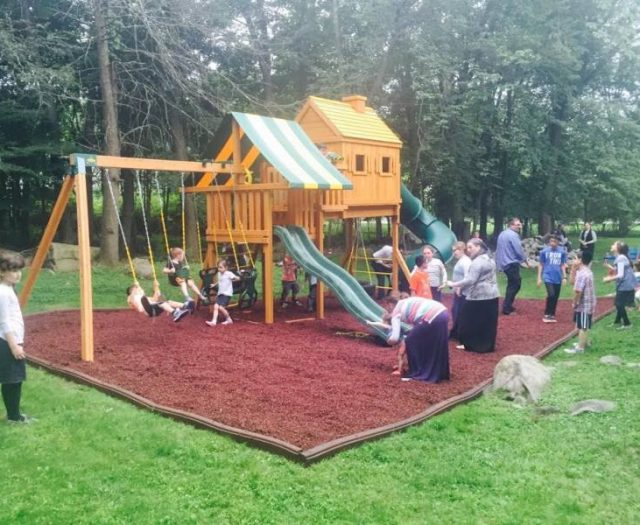 Fantasy Treehouse Cedar Swing Set Installed with Red Rubber Mulch With Happy Customers from Make A Wish
