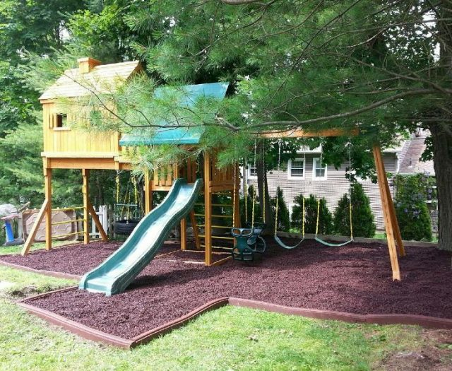 Fantasy Treehouse Outdoor Playset Installed in Brown Mulch With Green Tent and Slide