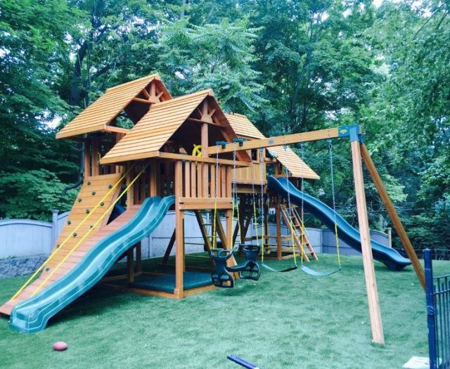 Imagination Swing Set installed in backyard with sand box wood roofs and step ladder