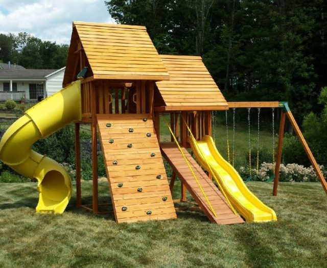 Sky Playset with wood roofs and gang plank installed in backyar