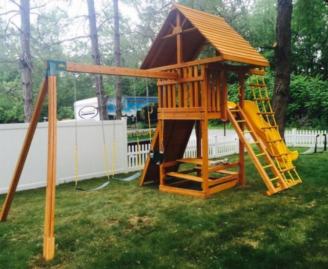 Ultimate Cedar Swing Set Installed in backyard with infants swing and picnic table
