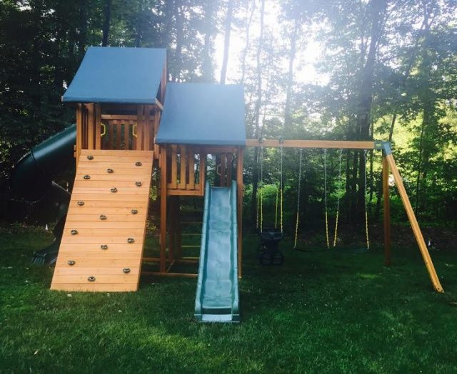 Wooden Sky Swing Set installed in backyard wiht green tent tops