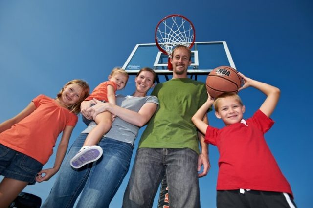 Family Standing Under Goalsetter Basketball Hoop