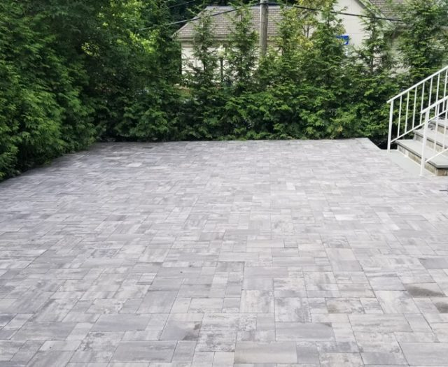 grey stone patio on side and back of home for outdoor family time
