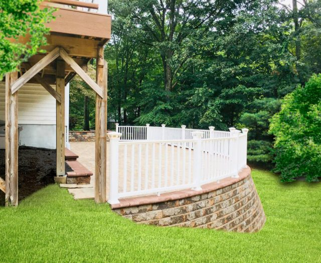 raised patio with stone wall and railing for backyard