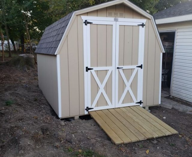 Barn Storage shed with double doors in yellow and white trim