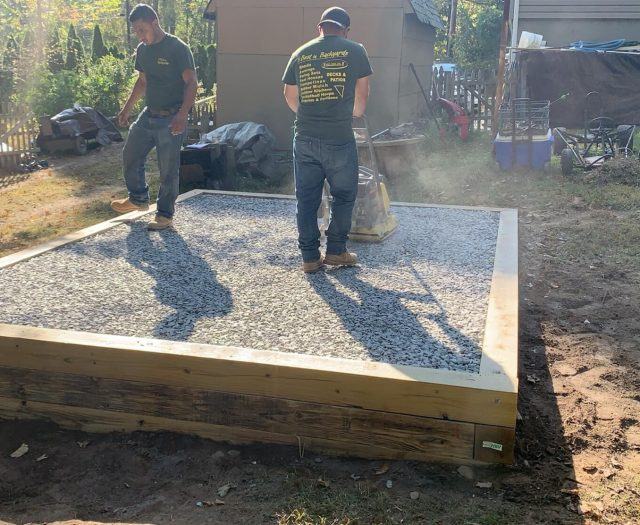 installers setting up gravel pad for shed
