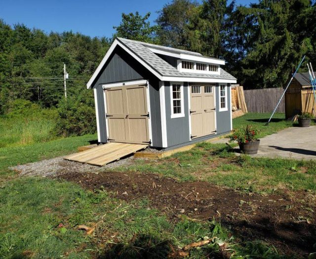 A-Frame Shed with Blue T-111 Siding, White Trim, Beige Double Doors, and Dormer