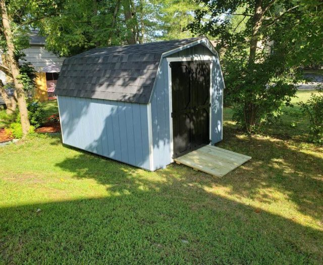 Barn Shed with Blue T-111 Siding, White Trim, and Black Door