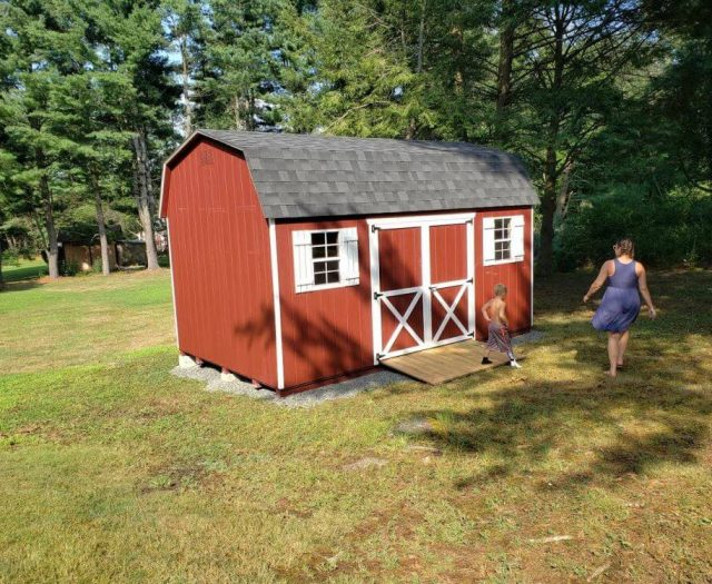 Dutch Barn Shed with Red T-111 Siding and Door and White Trim and Shutters