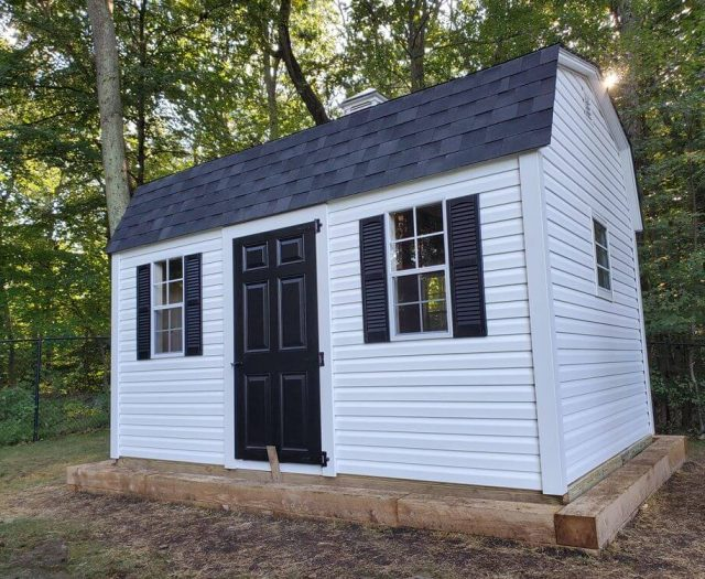 Dutch Barn Shed with White Vinyl Siding and Trim, Black Door and Shutters