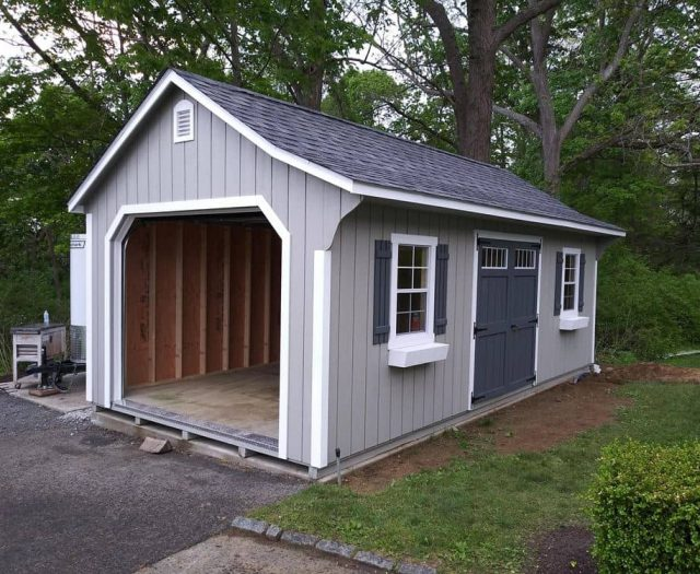 Cape Shed with T-111 Gray Siding Garage Door and Shutters with White Trim and Flower Boxes