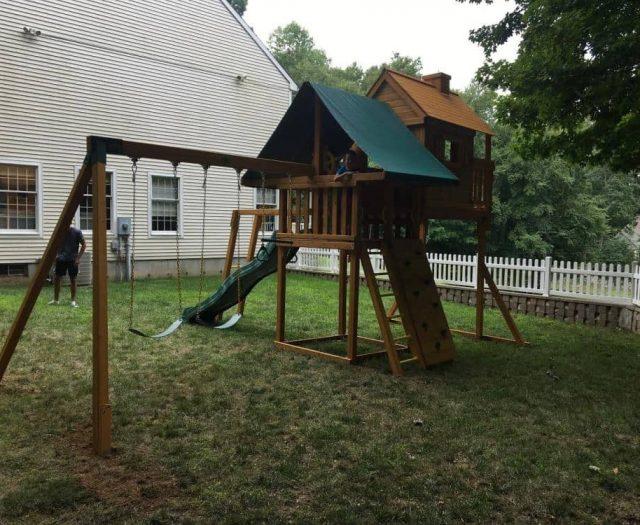 Sky Tree House Swing Set with Kid Posing