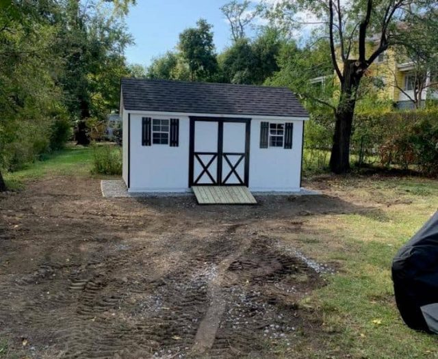 A- Frame Shed with White T-111 Siding, Black Trim and Shutters, and Wooden Ramp