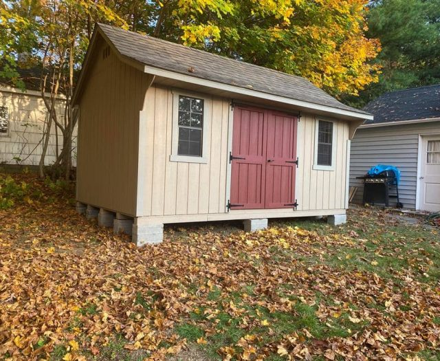 Cape Storage Shed with Tan T-111 Siding, Red Double Door, and White Trim