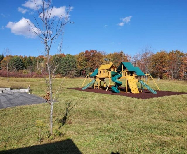 Imagination Swing Set with Rock Wall, Red Rubber Mulch, and Tire Swing