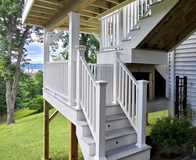 composite deck with white vinyl railings and dual staircase