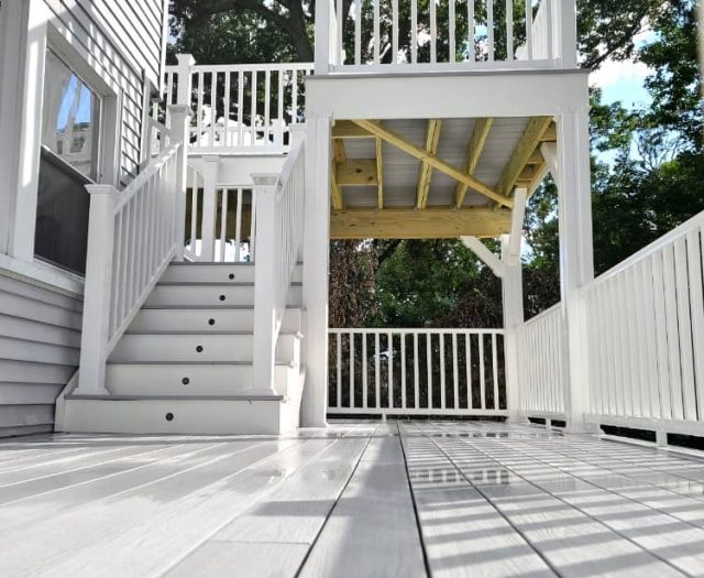 two story composite deck with white vinyl railings and staircase