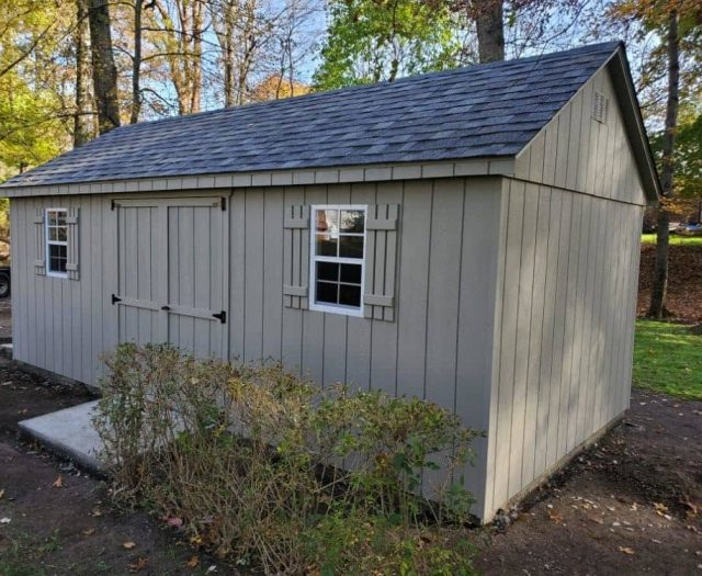 A- Frame Backyard Shed with Gray T-111 Siding, Windows, and Concrete Door Step
