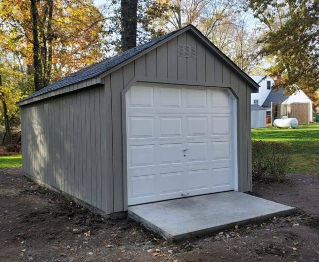 A- Frame Storage Shed with Green T-111 Siding, Garage Door, and Concrete Landing