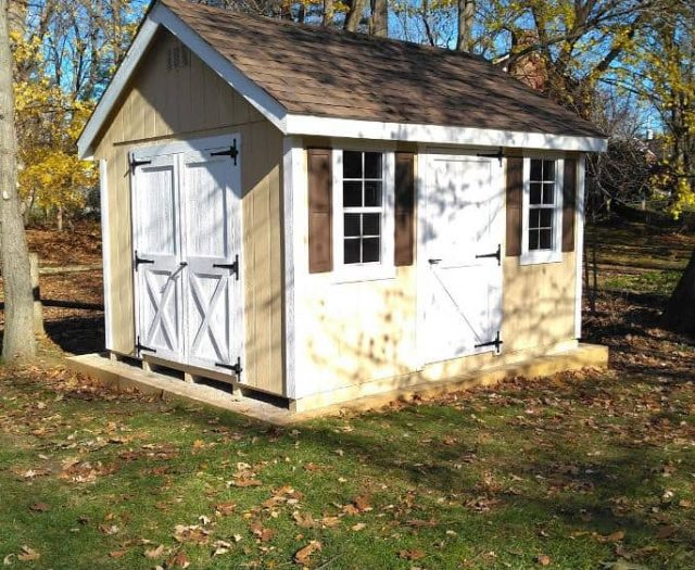 A- Frame Storage Shed with Yellow T-111 Siding, White Trim, and Brown Shutter