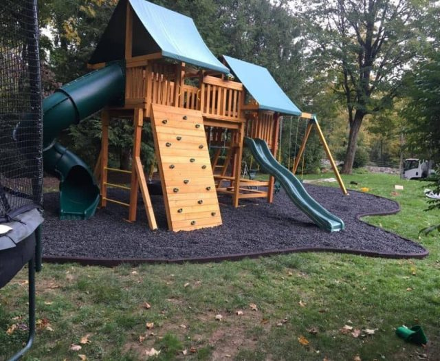 Fantasy Swing Set with Black Rubber Mulch, Rock Wall, and Spiral Slide