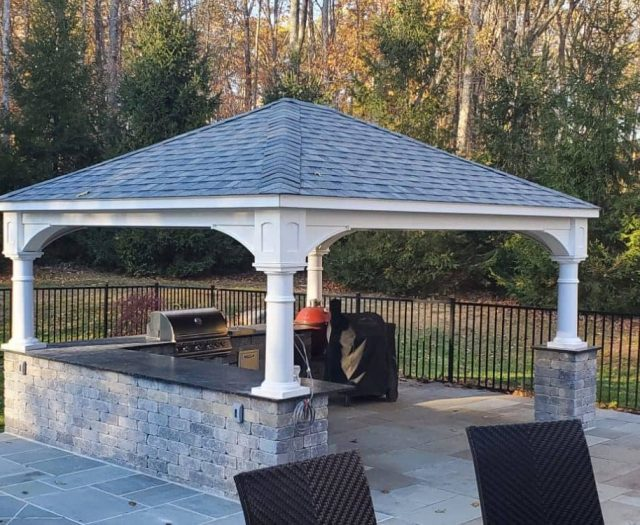Traditional Pavilion with White Vinyl on Top of Stone Outdoor Kitchen