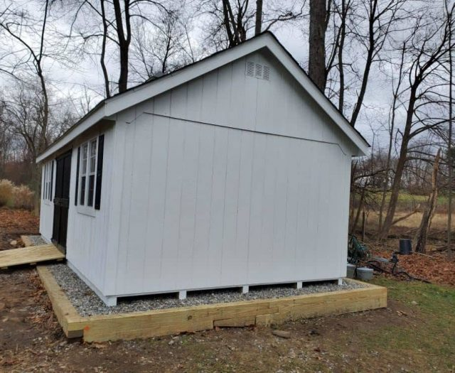 A- Frame Shed with White T-111 Siding, Vent, and Gravel Pad