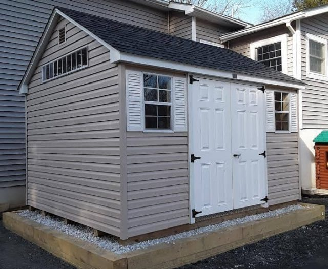 A-Frame Shed with Beige Vinyl Siding, White Shutters and White Double Doors