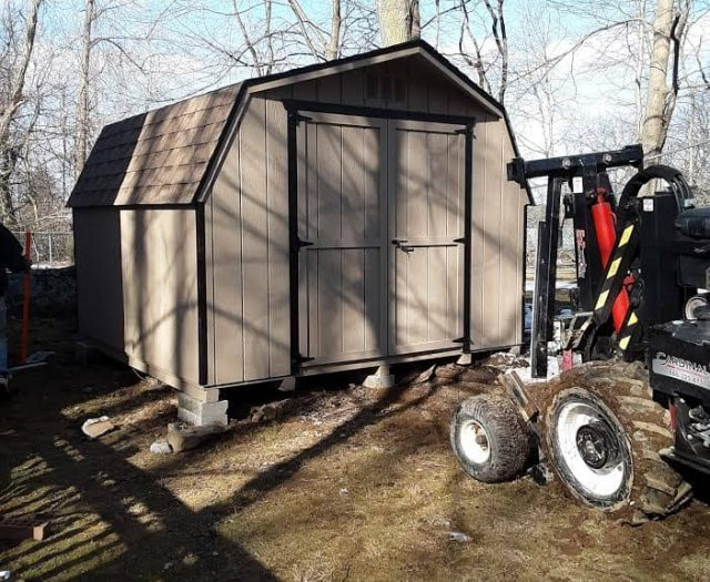 Barn Storage Shed with Brown T-111 Siding, Black Trim, and Tan Double Doors