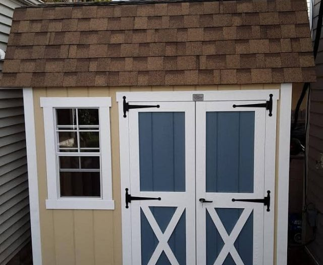 Dutch Barn Storage Shed with Yellow T-111 Siding, Blue Double Door, and White Trim
