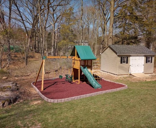 red rubber mulch and flexible border underneath dream playset