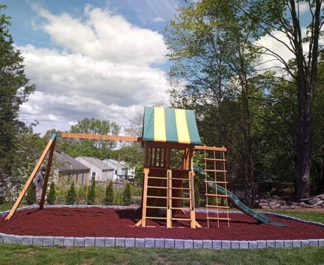 Supreme Swing Set with Red Rubber Mulch, Greystone Borders, and Double Clubhouse Ladder