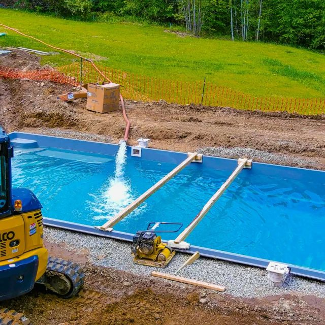 inground pool being lowered into the ground