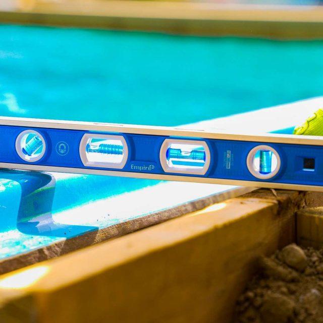 pool experts measuring length of fiberglass inground pool