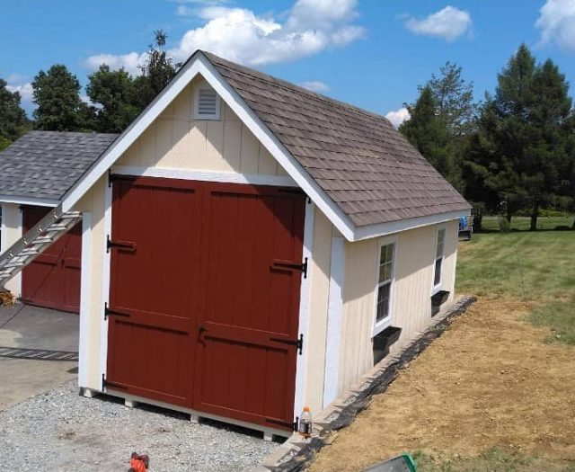 A Frame Shed with Beige T-111 Siding, Red Double Door, and White Trim