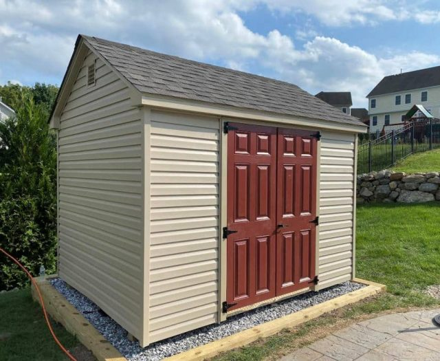 A-Frame Storage Shed with Beige Vinyl Siding, Red Double Doors and Beige Trim